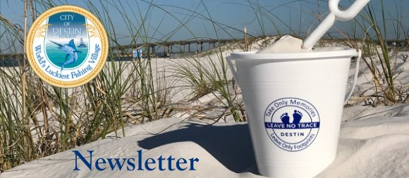 Sand pail in the sand with sea oats with Leave No Trace logo and city logo