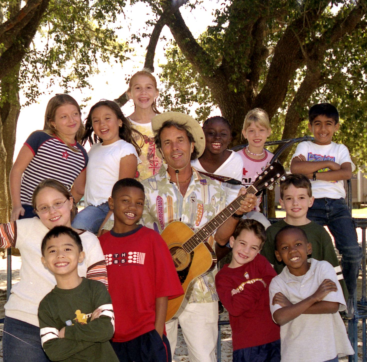 A picture of Mr. Mac holding his guitar with children surrounding him.