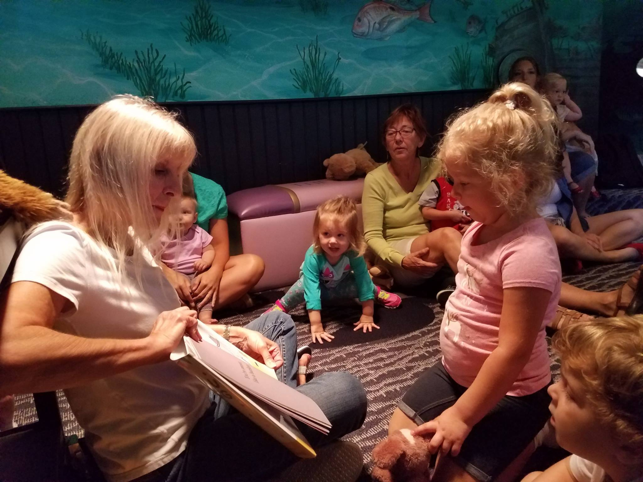 A woman holding a book reading to children