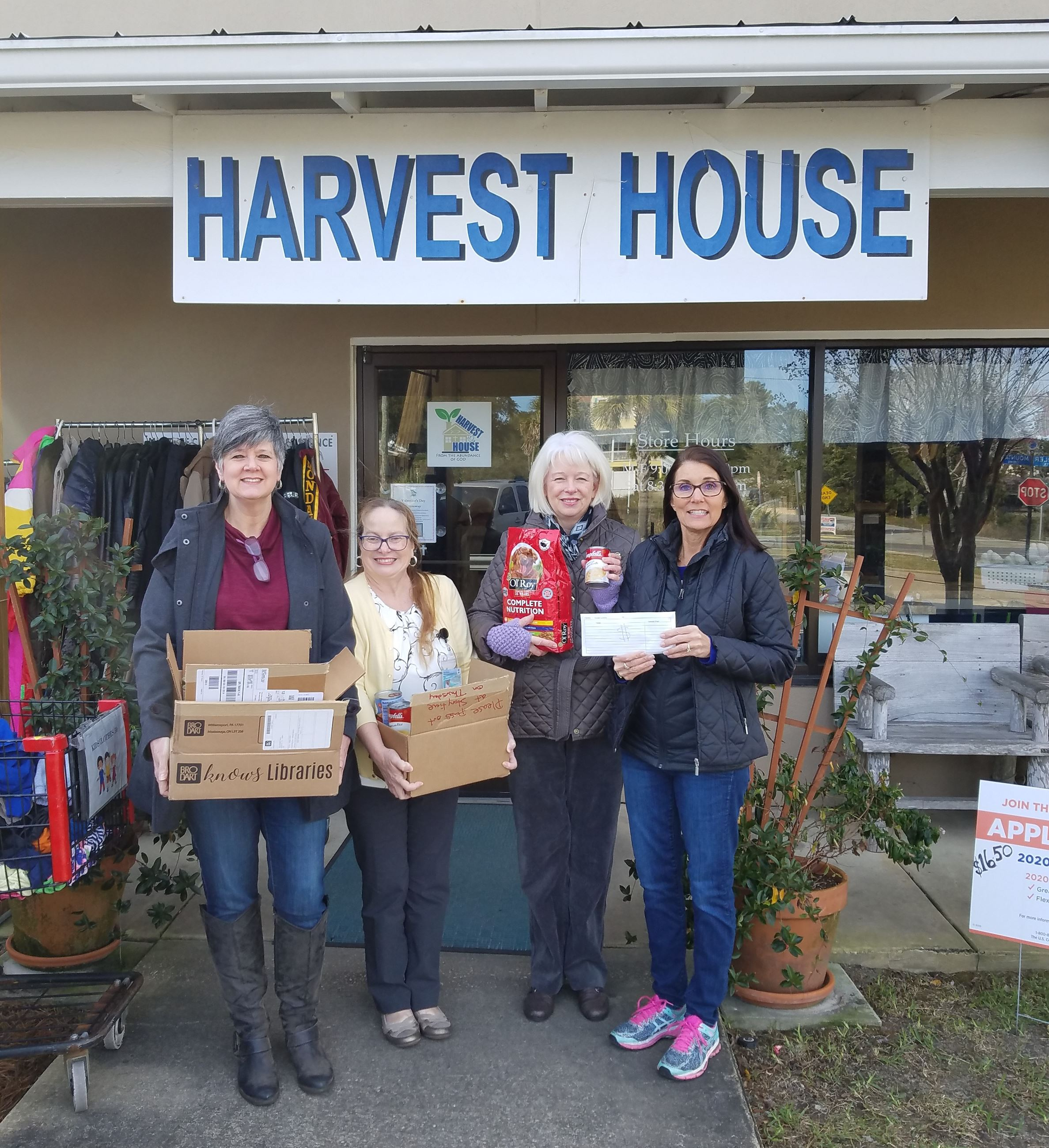 Picture of library staff and harvest staff holding the donations